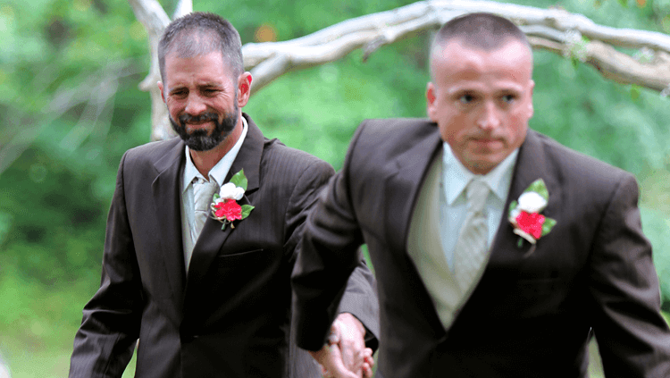 emotional wedding photo of dad and step dad